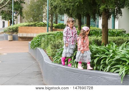 two young child girls, sisters, walking by street in auckland, new zealand