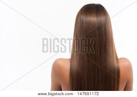 Young woman is standing with long smooth hair. Focus on her back. Isolated and copy space in left side