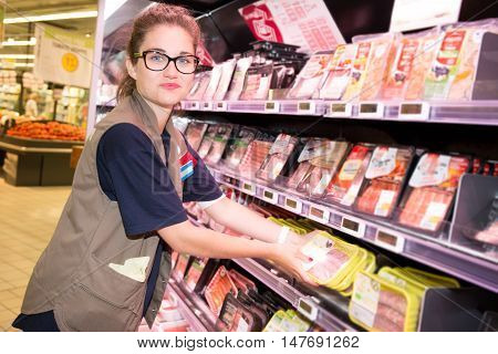 a Smiling supermarket employee standing among shelves