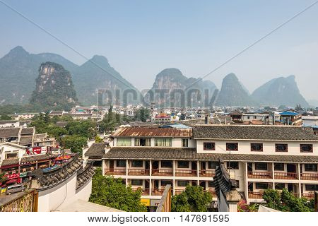 Yangshuo China - October 22 2013: View of the roofs and mountains in Yangshuo China. The town has become a resort destination for both domestic and foreign travelers.There is a lot to explore in Yangshuo.