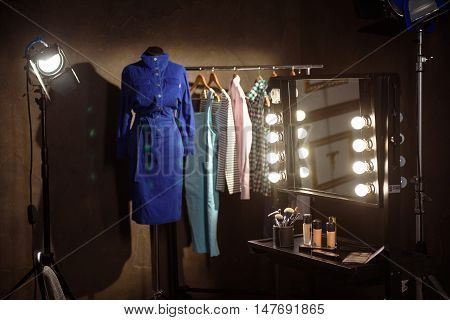 Cosmetic near mirror and collection of fashionable clothing hanging on rack backstage