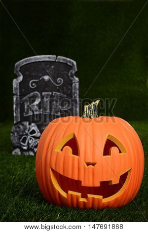 closeup of a pumpkin and tombstone on grass
