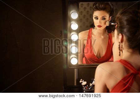 Confident female model is applying powder on her face. She is sitting near mirror and looking forward with concentration. Copy space in left side