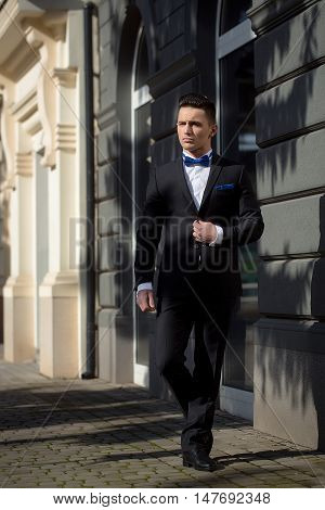 Young man wears suit and bow tie with confidence. Confident businessman.