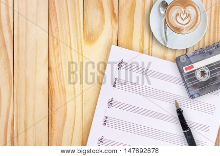 music paper, fountain pen, tape cassette and coffee latte on wooden table