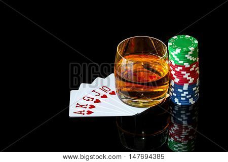 Cards with chips to play poker and tumbler of whiskey