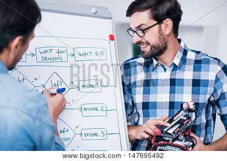 Involved in work. Cheerful man drawing a scheme on the board and working with his colleague who is holding robot