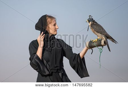 Woman in traditional emirati dress, called abaya, with falcon on her arm