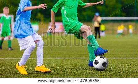 Football soccer game of youth teams. Running young players kicking soccer ball on sports field