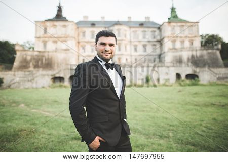 Stylish groom posing on background old castle.