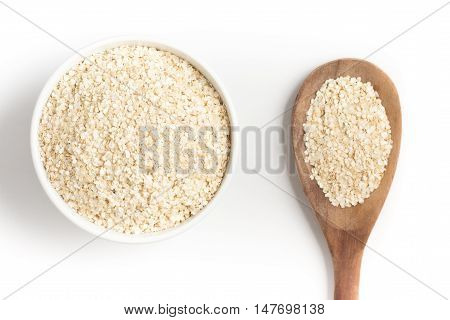 Quinoa Flakes into a bowl isolated in white background. Super Food.