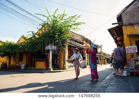 Hoi An, Vietnam - September 02, 2013: The tourist is taking photos in the street while the vendor is walking across