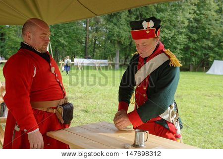 GATCHINA, ST. PETERSBURG, RUSSIA - SEPTEMBER 10, 2016: Soldiers in retro uniform of Russian Army play dice in the camp during the festival Gatchinskaya Byl. The festival is held first time this year