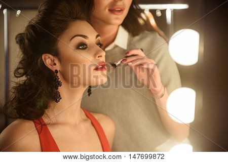 Professional female beautician is doing make-up for young woman. They are looking at mirror with satisfaction