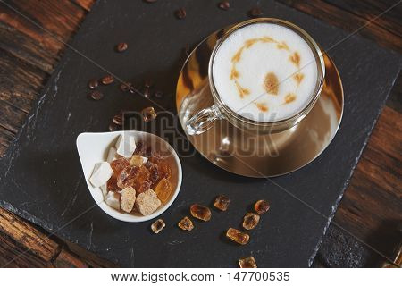 Fresh cappuccino in glass with sugar close up