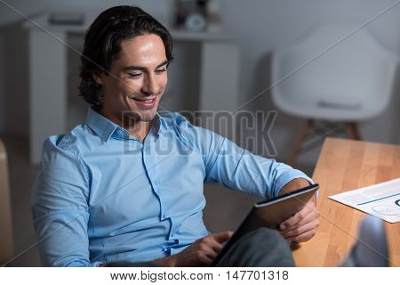 Modern user. Handsome young man sitting at the table and smiling while using tablet.