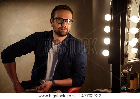 Confident young man is sitting near mirror backstage. He is looking forward with joy