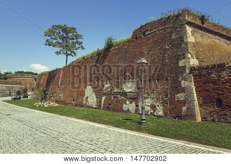 Majestic ruins of brick fortification walls and cobblestone alley of the spectacular medieval strategic fortress of White Carolina Citadel.