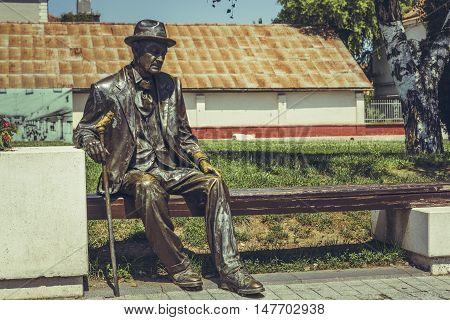Alba Iulia, Romania - July 24, 2016: Bronze statue depicting a sad and tired old fellow citizen resting on a bench in Alba Carolina Citadel square.