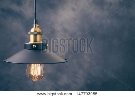 Retro light lamp with Edison light bulb at left of blurred background.Toned