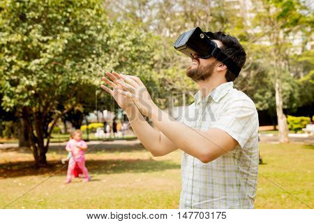 Young man wearing virtual reality goggles outside