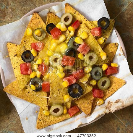Baked nachos with cheese green and black olives tomato and corn photographed overhead on slate with natural light