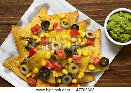 Baked nachos with cheese green and black olives tomato and corn with guacamole on the side photographed overhead with natural light (Selective Focus Focus on the top of the meal)
