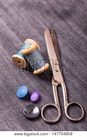 Scissors, sewing spools and buttons on fabric background