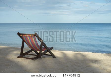 portrait of a beach chair on a white sand beach with bluesky and blue sea in background,selective focus,filtered image,rest moment,time to rest,perfect time