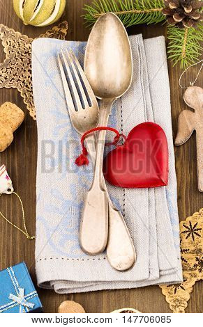 Silverware and christmas decorations around on table