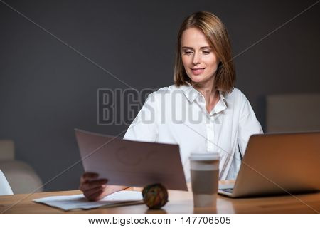 Nice work. Happy beautiful woman inspired by her favorite job discovering documents while working on a laptop in an office