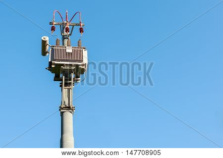 Electrical transformer to electrical pylon against the blue sky