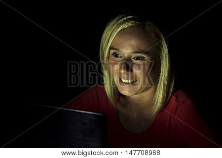 woman working on a computer by night in a dark room with only light from computer falling on her smiling face