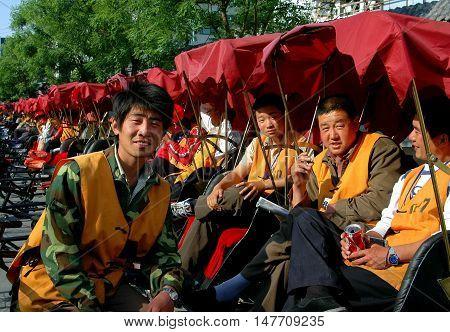 Beijing China - May 5 2005: Pedicab drivers sitting in their bicycle taxis waiting for fares at the Shi Sa Hai Hutong