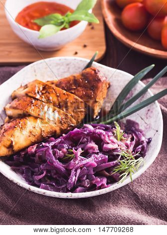 Stewed red cabbage and sliced chicken breast on plate.Toned