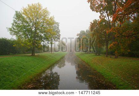 Cross the bridge and misty autumn morning in Alexandrovsky Park in Tsarskoye Selo