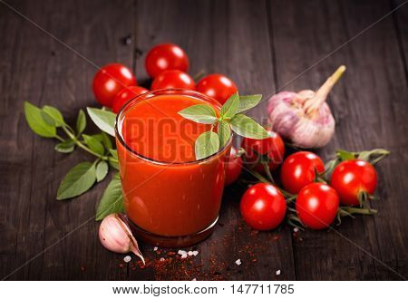Tomato juice glass with basil and tomatoes on a wooden table