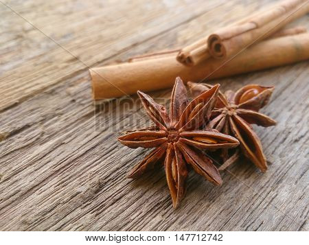 Star anise spice fruits and seeds isolated on wood background closeup