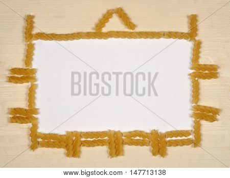 Pasta fusilli frame border background with the place for text. Top view.