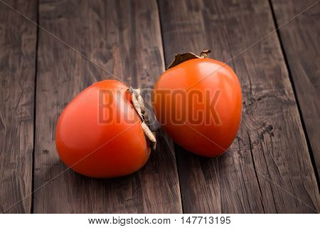 Two ripe orange persimmon on wooden table