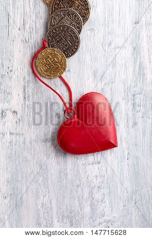 Vintage heart decoration and old coins on light blue background