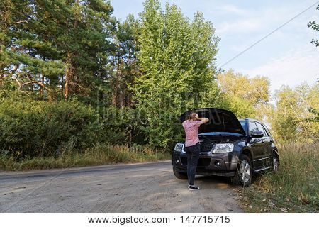 A Woman Looks At The Open Hood Of The Broken Car