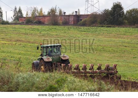 Farmer on tractor plowing the land in autumn
