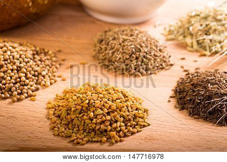 Whole spice piles including dried fenugreek, coriander and caraway