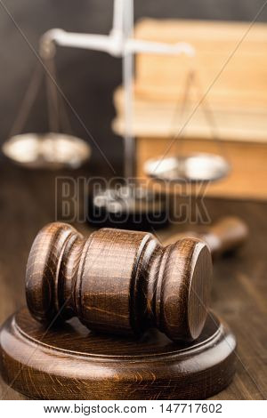 Wooden gavel with scales and books on table vertical