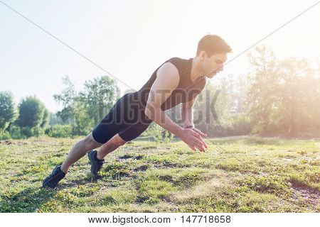 Fitness man doing clapping push-ups exercise intense training outdoors