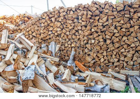 pinned and stacked firewood in the yard on summer day