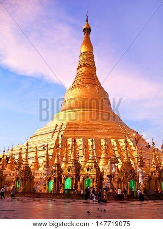 YANGON, MYANMAR - JANUARY 3, 2011: Pilgrims walking around golden Shwedagon Paya at sunrise.