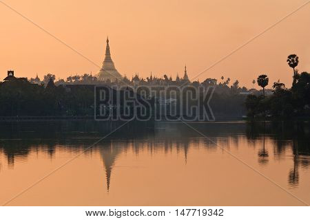 Golden Shwedagon Pagoda at sunrise in Yangon Myanmar - view from Kandawgyi lake. The pagoda is situated on Singuttara Hill and dominates the Yangon skyline.