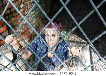 punk girl sitting on the floor behind metal bars in the dark room of hte abandoned castle closeup